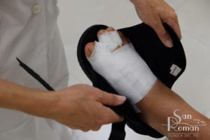 putting on special postoperative shoes